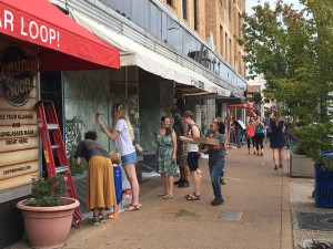 Artists painting plywood covering broken windows, Delmar Blvd., St. Louis